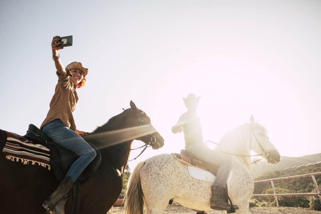 Horse riders using a mobile phone